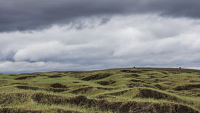 Black and Green Volcanic Landscape Iceland. Volcanic landscape on Iceland with grass, lava and black sand and dark rain clouds in the sky Royalty Free Stock Photo