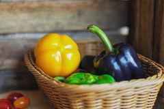 Black, green and yellow paprika`s in a wicker basket. Stock Photo