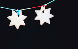 Black Greeting Background With Gingerbread. Two hanging ginger biscuits in the shape of a star on a black backdrop. Greeting card, holiday background with space Royalty Free Stock Image