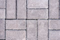 Black and grey cobblestones of a footpath have been laid in a geometrical pattern. royalty free stock images
