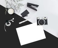 Black and grey color background with flower branches, a cup of milk, earphone, pen, stapler, camera, name card and white paper. Architect and designer stock images