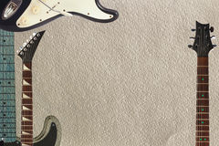 Black and grey electric guitars and two necks on rough cardboard background, with plenty of copy space. Black and grey electric guitars and two necks on the stock photography