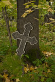 Black with grey rim mosaic Orthodox cross on an old autumn cemetery. Black with grey rim mosaic decorated Orthodox Christian cross on an old autumn cemetery Royalty Free Stock Photography