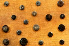 Black and grey sewing buttons on wood. Black and grey sewing buttons of different sizes on an old wooden background Stock Photos