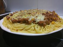 Melted organic cheddar cheese with spaghetti bolognese. With black ground pepper on top stock images