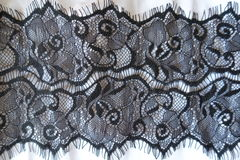 Black guipure lace over white cotton fabric Royalty Free Stock Image