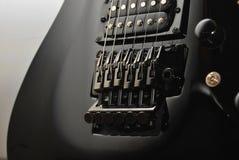 Black guitar. Detail of black e-guitar on white background Stock Images