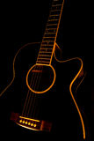 Black guitar. A black guitar with a black background Royalty Free Stock Photo