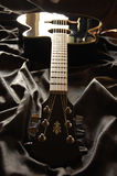 Black Guitar. Black acoustic guitar on black silk stock photography