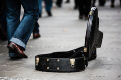 Black Guitar Case on Concrete Pathway With People Walking during Daytime Royalty Free Stock Image