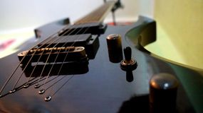 A black guitar. A black glossy electro guitar stock photography