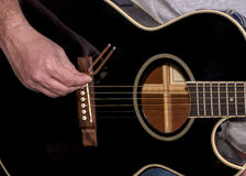 Black guitar and tuning fork. Using a tuning fork on guitar to get it in tune Royalty Free Stock Photography