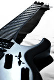 Black Guitar in white. Black metal guitar seen from the bottom with white background Royalty Free Stock Image