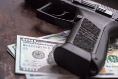 Black gun on American dollars background. Military industry, war, global arms trade, weapon sale, contract killing stock photo