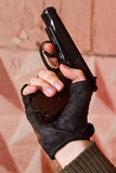 Gun in his hand in a black glove Stock Image