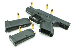 Black gun and 9mm bullets  a white background.  Stock Image