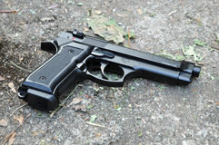 Black gun 9mm. Black 9mm gun on a road Royalty Free Stock Image