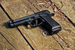 Black gun 9mm. Black 9mm gun on a wooden floor Royalty Free Stock Image