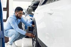 Free Black Guy Checking Car Wheels And Tyres In Dealership Showroom Royalty Free Stock Photos - 185061408