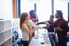 African and Hindu coworkers with their supporters arguing at work. Black guy disputing with Indian partner. verbal duel. verbal skirmish. African and Hindu stock photos