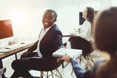 A black guy gives a notebook to a girl in the office. They work in the call center. The men is smiling Stock Photo