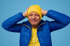 Black guy having migraine from distorted sound. Stylish African male in bright outfit suffering from awful headache and covering ears against blue background stock photography