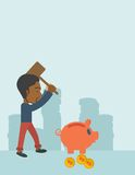 Black guy holding a hammer breaking piggy bank. A black businessman standing while holding a hammer breaking piggy bank with dollar coins for financial Royalty Free Stock Images