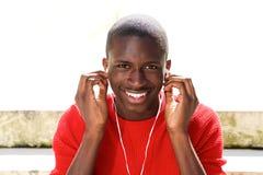 Black guy listening music on earphones. Portrait of happy black guy sitting outdoors and listening music on earphones Royalty Free Stock Photos