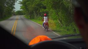 Black guy on a motorcycle traveling on the road. From the car windows stock video footage