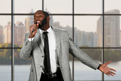 Black guy sings into microphone. Royalty Free Stock Photography
