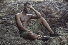 Black guy sits on the rocky shore Stock Image