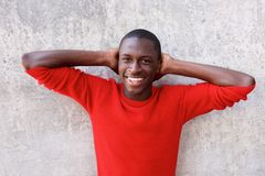 Black guy standing with hands behind head and smiling Stock Photos