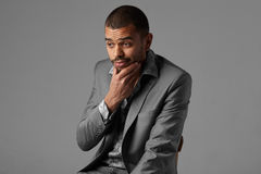Black guy thinking in gray blazer isolated on gray background Stock Photography