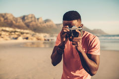 Black guy using digital camera on beach. Afro american man taking pictures on the seashore Stock Images
