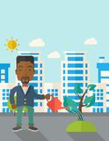 Black guy watering the plant Royalty Free Stock Photography