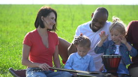 Black guy and white woman with two white children on a picnic. The woman looks like an African American is stroking a white boy on the head, and a little girl is stock video