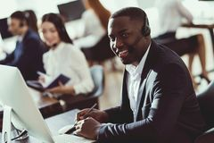 A black guy works in a call center. He has headphones on which they talk with customers. He is an operator and he answers questions stock photography