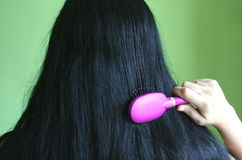 Black hair. And a pink comb stock image
