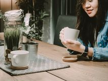 Black hair asian hipster girl 25s to 35s with blue jacket jean. During smile relax and drink coffee for wait her friend with soft focus decoratation background Royalty Free Stock Images