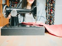 Black hair asian hipster girl 25s to 35s with blue jacket jean. During use black sewing machine with soft focus background Royalty Free Stock Image