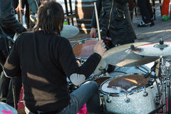 Black hair drummer during outdoor concert: rear view Stock Photo