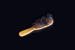 Black hair loss problem with hairbrush on dark backgroud Stock Photography