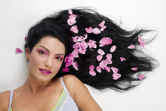 Black hair with pink rose petals royalty free stock photo