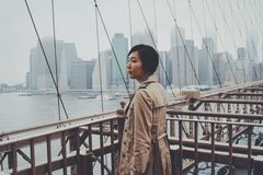 Black Hair Woman in Brown Coat on Grey Metal Bridge Stock Photo