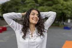 Black hair woman hands over head looking at side sitting outdoor. Black hair woman hands over head looking at side Stock Photography