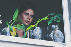 Black Haired Female Looking Outside the Window Stock Photography