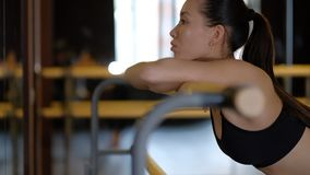 Black haired girl dancer with ponytail leans on ballet machine handrail and rests close side view slow motion.  stock video