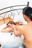 Black-haired man massaging his wife Stock Photos