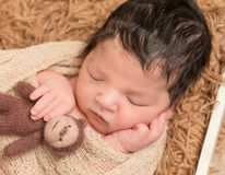 Black-haired newborn with monkey toy, closeup Stock Images