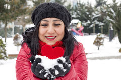 Black haired Turkish women holding a red heart in her hand and celebrating Valentine's day with snowy background Royalty Free Stock Image